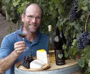 Professor James Luby in the vineyard with wine and cheese