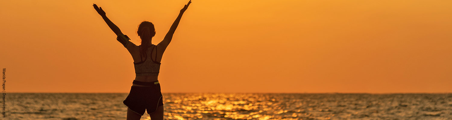 Person with arms outstretched to sunset