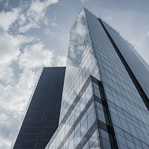 A low-angle shot of a skyscraper, whose glassy surface reflects a partially cloudy sky.