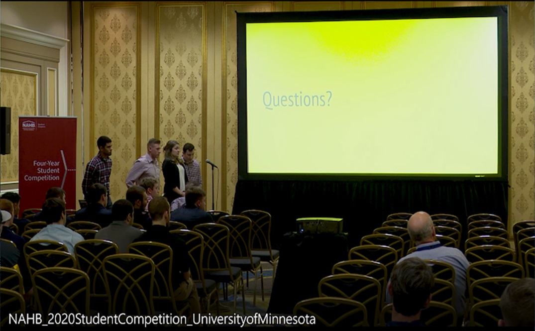 students standing in line at a microphone in front of a projector presentation