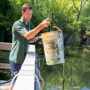 Ben Minerich pulling a bucket of mussels out of a pond