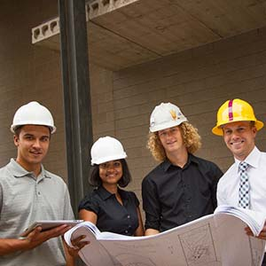 four people in hardhats holding blueprints