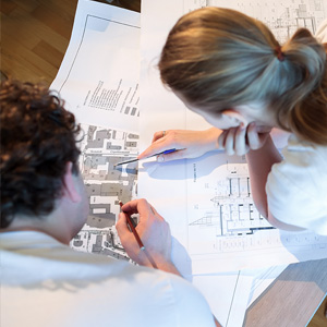 image of 2 people looking at construction plans