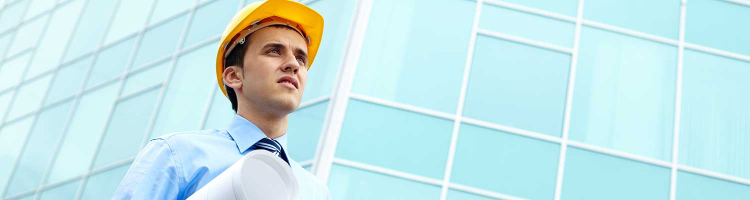 Man in hard hat holding blueprints outside a building