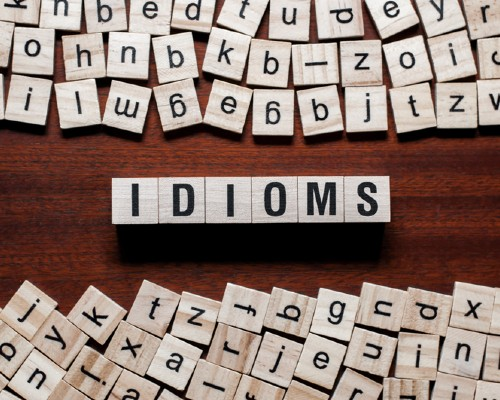 "Photo of Scrabble tiles spelling out ""Idioms"""