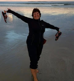 Portrait of Deb Fineman frolicking on a beach.
