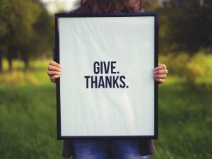 "A woman holds a framed portrait that reads ""Give. Thanks."""