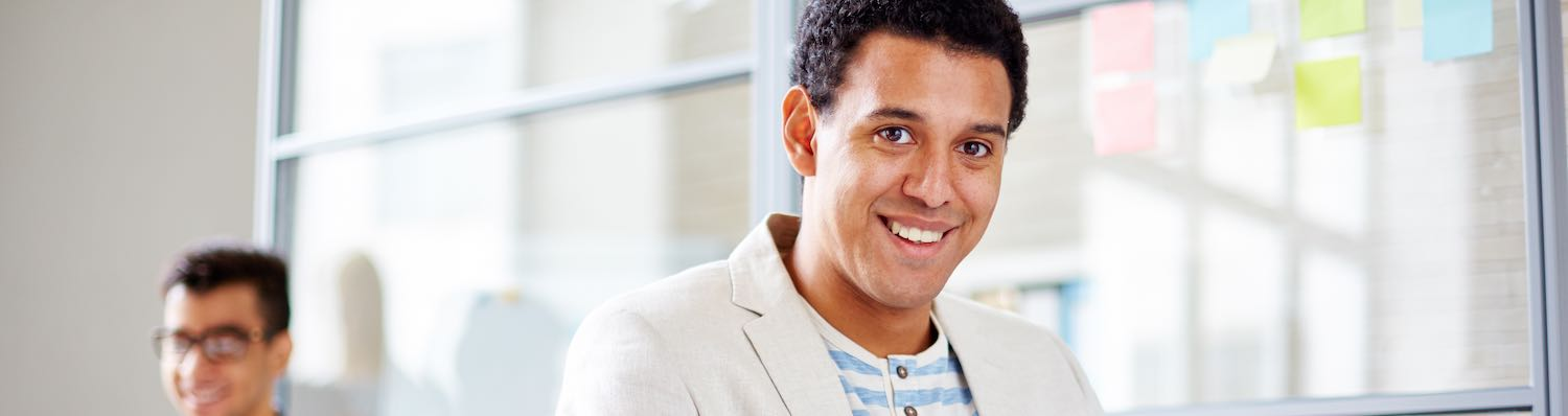 Man smiling at camera in office with coworker in background