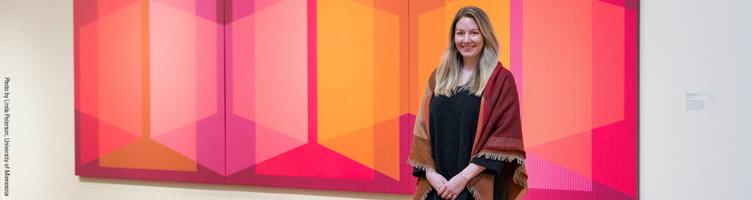 Katie Covey in front of painting in Weisman Museum