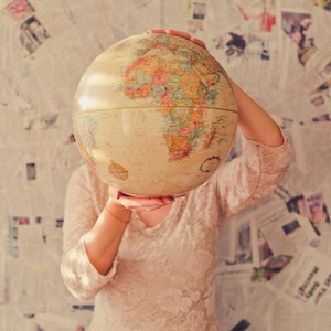 Photo of a woman holding a vintage globe in front of her face.