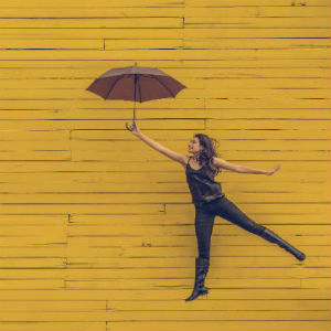 woman leaping against yellow wall with open umbrella held by outstretched arm