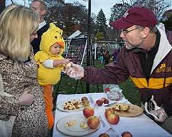 Professor James Luby hands out apple slices at Halloween party at Eastcliff