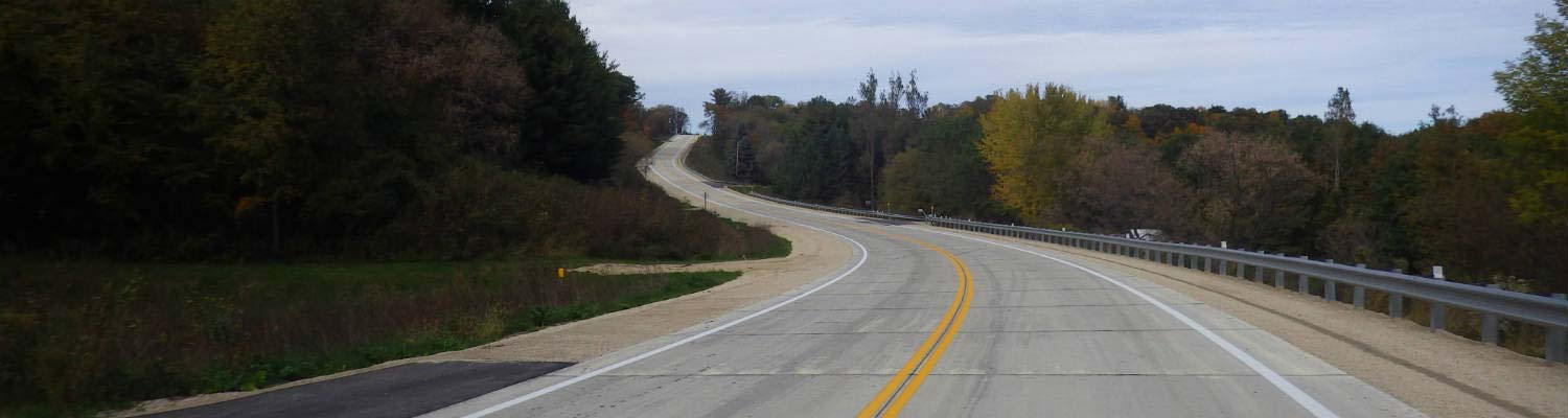 Highway curving through wooded landscape