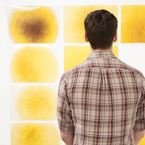 Man looking at yellow abstract painting