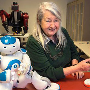 Dr. Maria Gini smiles, posing with a small humanoid robot upon a red table.