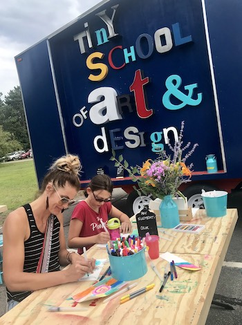 A woman and girl drawing at a table in front of the Tiny School of Art and Design truck