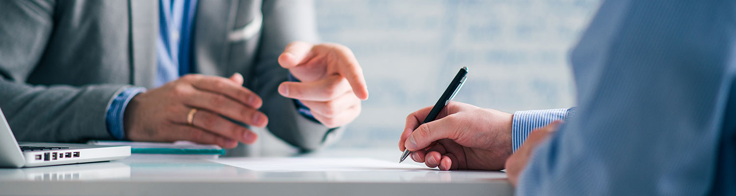 The hands of two men in business suits, one is writing with a pen on paper and the other gesturing toward the paper