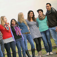 Group of diverse young people standing arm in arm