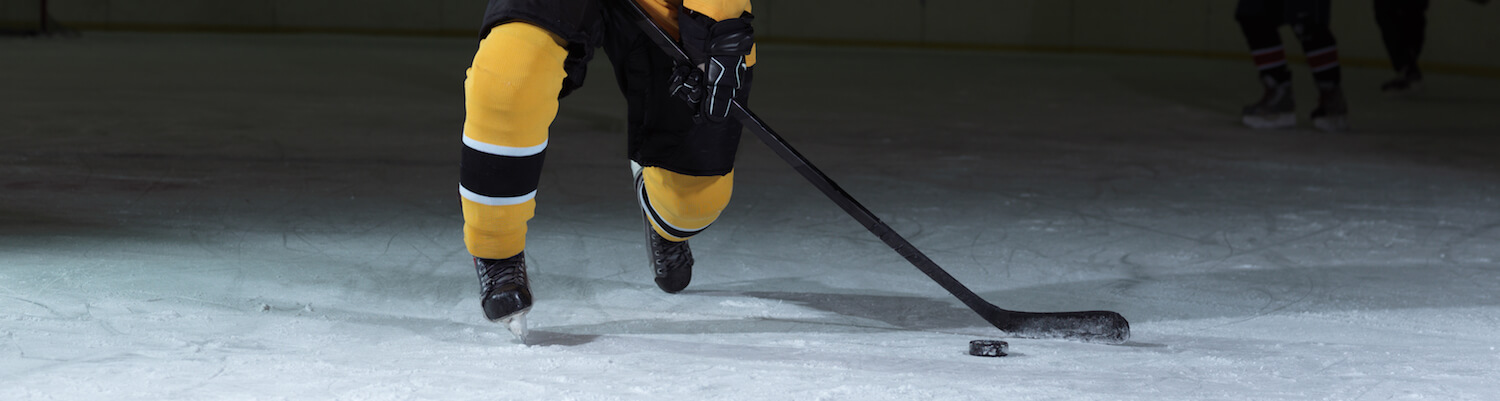 Hockey player legs, stick, and puck