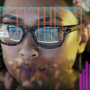 Woman looking at data on screen which is reflected in her glasses