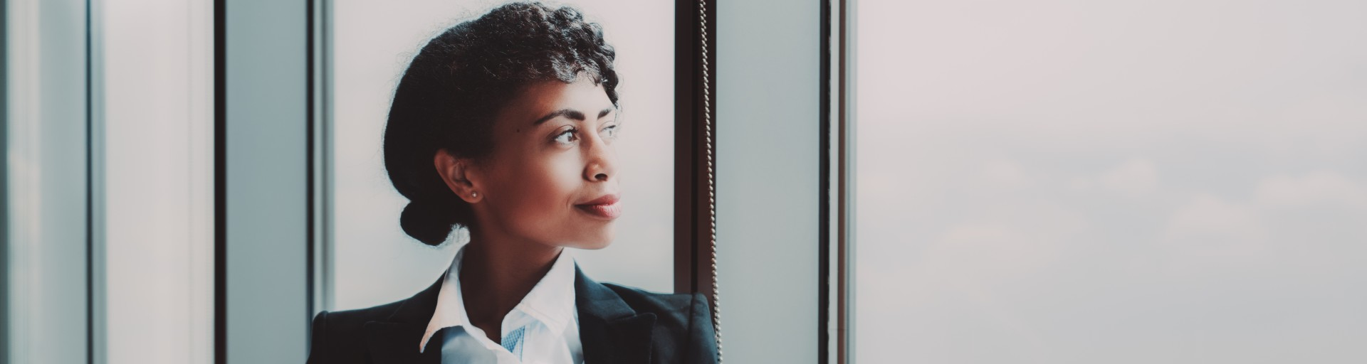 Biracial woman gazes out a large office window