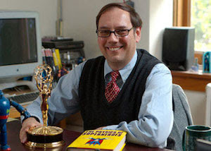 James Kakalios sits behind his desk with an Emmy award and a copy of his book.