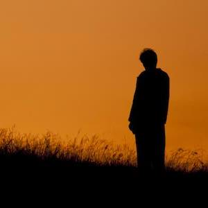 Silhouette of a man standing outside at sunset